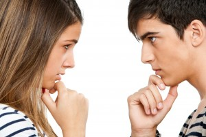 Close up portrait of teen couple looking at each other with wondering expression.Isolated on white.